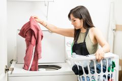 Ung husa som sätter smutsig kläder för wash i maskin arkivfoto
