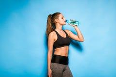 Ung idrotts- kvinna med en flaska av vatten royaltyfria bilder