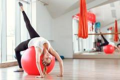 Ung idrotts- kvinna som gör övningar med konditionbollen i idrottshall Royaltyfri Bild