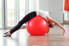 Ung idrotts- kvinna som gör övningar med konditionbollen i idrottshall Royaltyfria Bilder