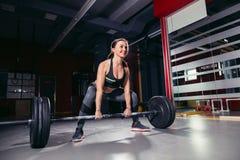 Ung idrotts- kvinna som gör deadlift med skivstången Arkivbild