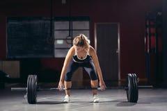 Ung idrotts- kvinna som gör deadlift med skivstången Fotografering för Bildbyråer