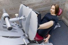Ung idrotts- kvinna som g?r ?vningar p? ben och bakdelar i idrottshall Sport kondition, bodybuilding, utbildning, sund livsstil fotografering för bildbyråer