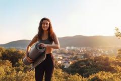 Ung idrotts- kvinna som rymmer en yoga matt Begreppet av sporten, kondition och den sunda livsstilen Fjällnära solnedgång och by  royaltyfria foton