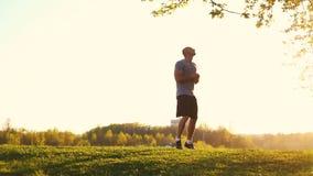 Ung idrotts- löpare som gör sträcka övningen som förbereder sig för genomkörare i parkera solnedgång tonad video arkivfilmer