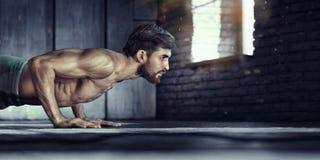 Ung idrotts- man som gör push-UPS arkivbild