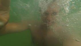 Ung idrotts- mandanandeselfie i havet och dykning under vatten i ultrarapid lager videofilmer