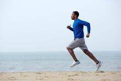 Ung idrotts- manspring på stranden Royaltyfria Foton