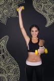Ung idrottskvinna som sätter upp en hand, medan utbilda med handvikter Royaltyfri Foto