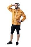 Ung idrottsman i omslag med hörlurar som täcker ögon från solljus som ser avstånd royaltyfri fotografi