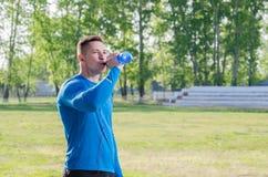 Ung idrottsman nen i hörlurardricksvatten arkivfoto