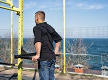 Ung idrottsman nen On Parallel Bars i en utomhus- idrottshall arkivfoton