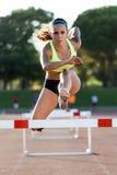 Ung idrottsman nen som hoppar över en häck under utbildning på lopptrac Royaltyfri Foto