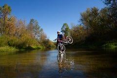 Ung idrottsman nen som korsar stenig terräng med cykeln i hans händer Fotografering för Bildbyråer