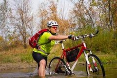 Ung idrottsman nen som korsar stenig terräng med cykeln i hans händer Arkivfoton