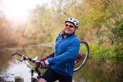 Ung idrottsman nen som korsar stenig terräng med cykeln i hans händer Royaltyfri Fotografi