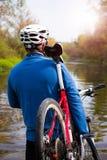 Ung idrottsman nen som korsar stenig terräng med cykeln i hans händer Arkivbilder