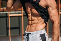 Ung idrottsman nen som poserar med en torso för fotografi på en bakgrund för tegelstenvägg Kroppsbyggare idrottsman nen med pumpa Arkivbilder