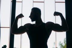 Ung idrottsman nen som poserar med en torso för fotografi på en bakgrund för tegelstenvägg Kroppsbyggare idrottsman nen med pumpa Fotografering för Bildbyråer