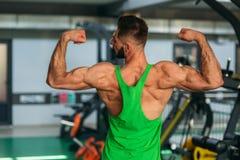Ung idrottsman nen som poserar med en torso för fotografi på en bakgrund för tegelstenvägg Kroppsbyggare idrottsman nen med pumpa Arkivfoto