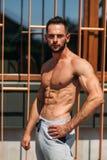 Ung idrottsman nen som poserar med en torso för fotografi på en bakgrund för tegelstenvägg Kroppsbyggare idrottsman nen med pumpa Royaltyfri Fotografi