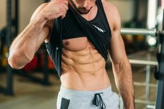 Ung idrottsman nen som poserar med en torso för fotografi på en bakgrund för tegelstenvägg Kroppsbyggare idrottsman nen med pumpa Arkivfoton