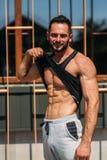 Ung idrottsman nen som poserar med en torso för fotografi på en bakgrund för tegelstenvägg Kroppsbyggare idrottsman nen med pumpa Royaltyfria Foton