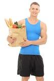 Ung idrottsman nen som rymmer en påse full av livsmedel Royaltyfri Bild