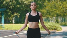 Ung idrottsman nen Woman i bekvämt rep för sportdräktbanhoppning på ett sportfält i parkera arkivfilmer