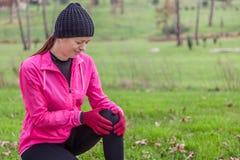 Ung idrottsman nenkvinna som gör ont från en knäskada arkivfoto