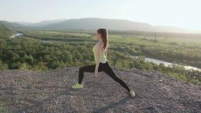 Ung idrottsman nenkvinna som värmer upp för konditiongenomkörare på soluppgång i morgonen Flicka som gör sträckning utomhus i arkivfilmer