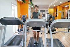 Ung idrottsman nenspring på tapis som är roulant i idrottshallen - begrepp för livsstil för konditionwellness sunt Arkivbild
