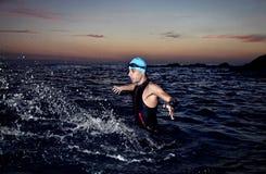 Ung idrottsman nentriathlon framme av en soluppgång Arkivfoto