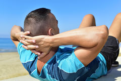 Ung idrottsman som gör buk- övningar Arkivbild