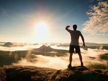Ung idrottsman som skuggar ögon från den ljusa solen, bergtoppmöte Arkivbilder