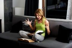 Ung ilsken kvinna som lär till examen på en soffa royaltyfria bilder