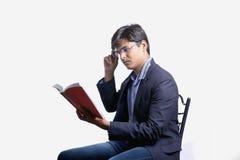 Ung indier på dräkt och läseboken royaltyfri foto