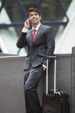 Ung indisk affärsman som meddelar på mobiltelefonen, medan stå bredvid bagagepåse Arkivfoton