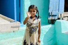 Ung indisk flicka som in camera ler och vinkar förbi handen i det fria 11 februari 2018 Puttaparthi, Indien Arkivfoton