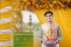 Ung indisk man med Lord Ganesha som firar den Ganesh festivalen arkivfoton