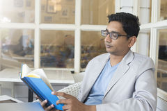 Ung indisk manlig läsning Fotografering för Bildbyråer