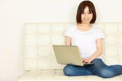 Ung japansk kvinna med datoren Fotografering för Bildbyråer