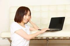 Ung japansk kvinna med datoren Arkivbilder