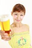 Ung japansk kvinna med ett exponeringsglas av öl Arkivbild