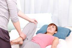 Ung japansk kvinna som får chiropractic Arkivfoto