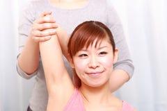 Ung japansk kvinna som får chiropractic Arkivbilder