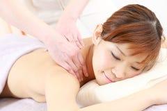 Ung japansk kvinna som får en massage Arkivbild