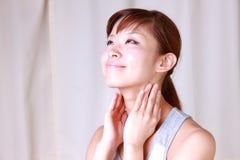 Ung japansk kvinna som gör en massage  för lymfaknutpunkt Arkivfoto