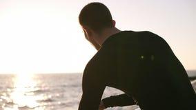 Ung jogger som lite stoppas för att ha att vila för långdistans- spring Han bär en svart skjorta för sportar med vit arkivfilmer
