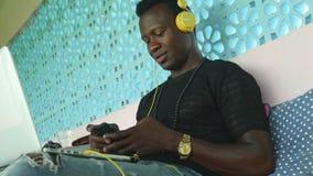 Ung kall och attraktiv svart afrikansk amerikanhipsterman med att knyta kontakt för hörlurar som kopplas av med mobiltelefonen oc stock video